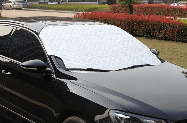 Gambar ini menunjukkan sebuah Mobil warna hitam dengan kaca depan Mobil tertutup
