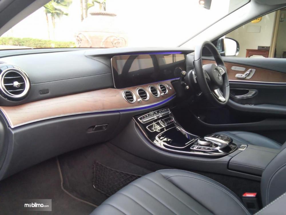 bagian dashboard Mercedes-Benz E350 EQ 2018 dengan aksen kayu, lining krom, dan lampu ambient berwarna biru