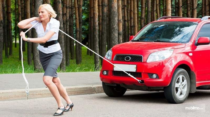 Gambar wanita menyeret mobil