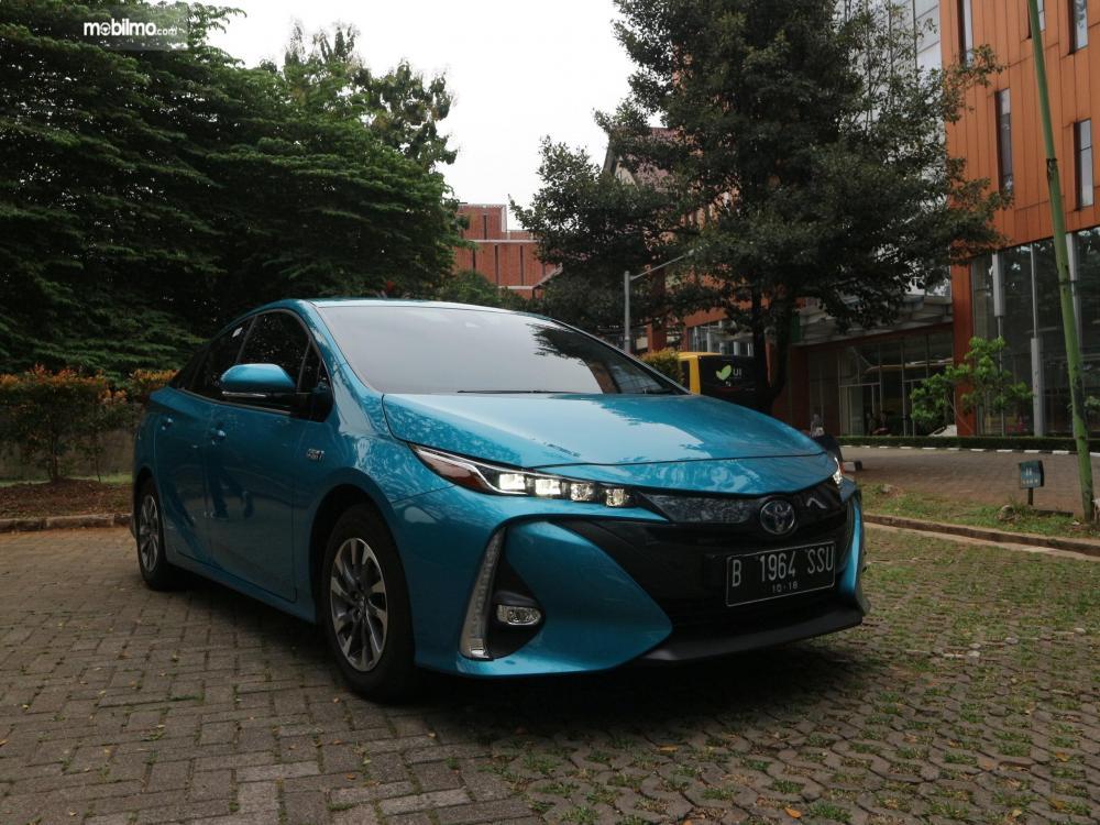 Tampak depan sebuah Toyota All New Prius PHV 2019 berwarna biru sedang parkir di lapangan yang luas