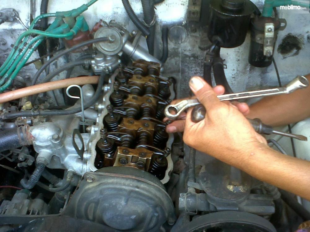 Gambar seorang mekanik sedang melakukan pemeriksaan klep