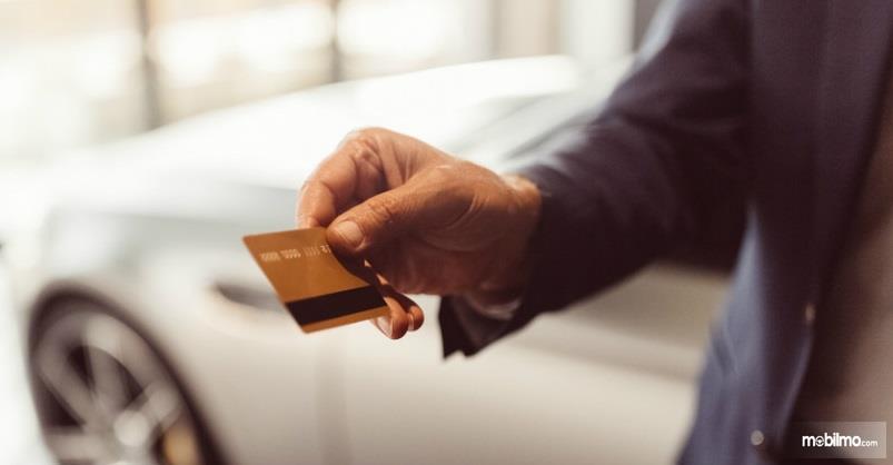 Gambar yang menunjukan pembeli yang membeli mobil dengan kredit