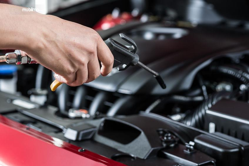 Gambar yang menunjukan teknisi yang sedang merawat mobil bekas
