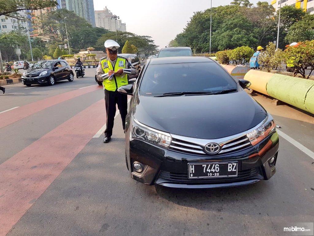 Foto seorang petugas menghentikan mobil yang melanggar aturan lalu lintas