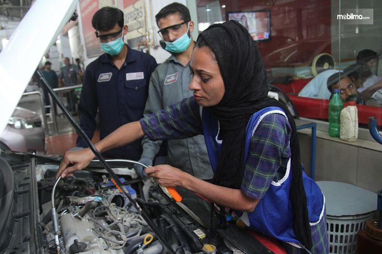 Gambar yang menunjukan Uzma Nawaz memperbaiki mesin mobil