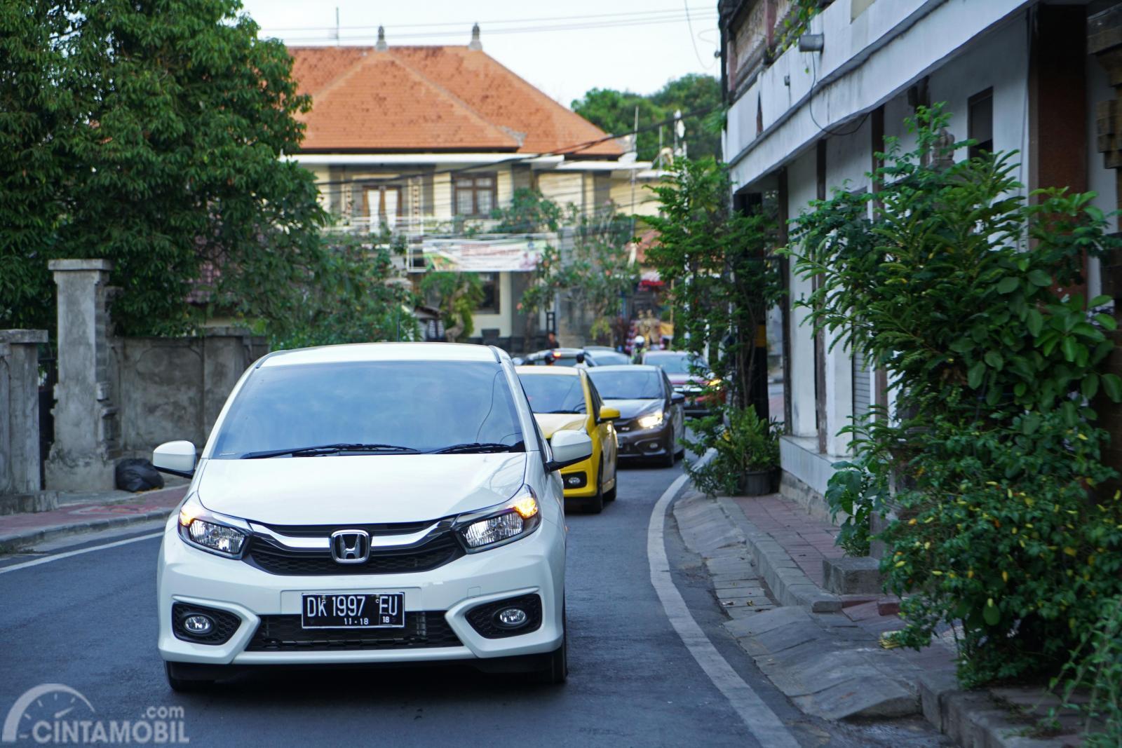Tampak sebuah All New Honda Brio Satya sedang melintasi jalan desa
