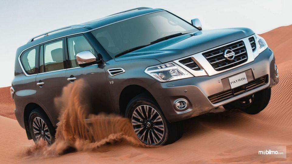 Gambar yang menunjukan Nissan Patrol diatas gundukan pasir