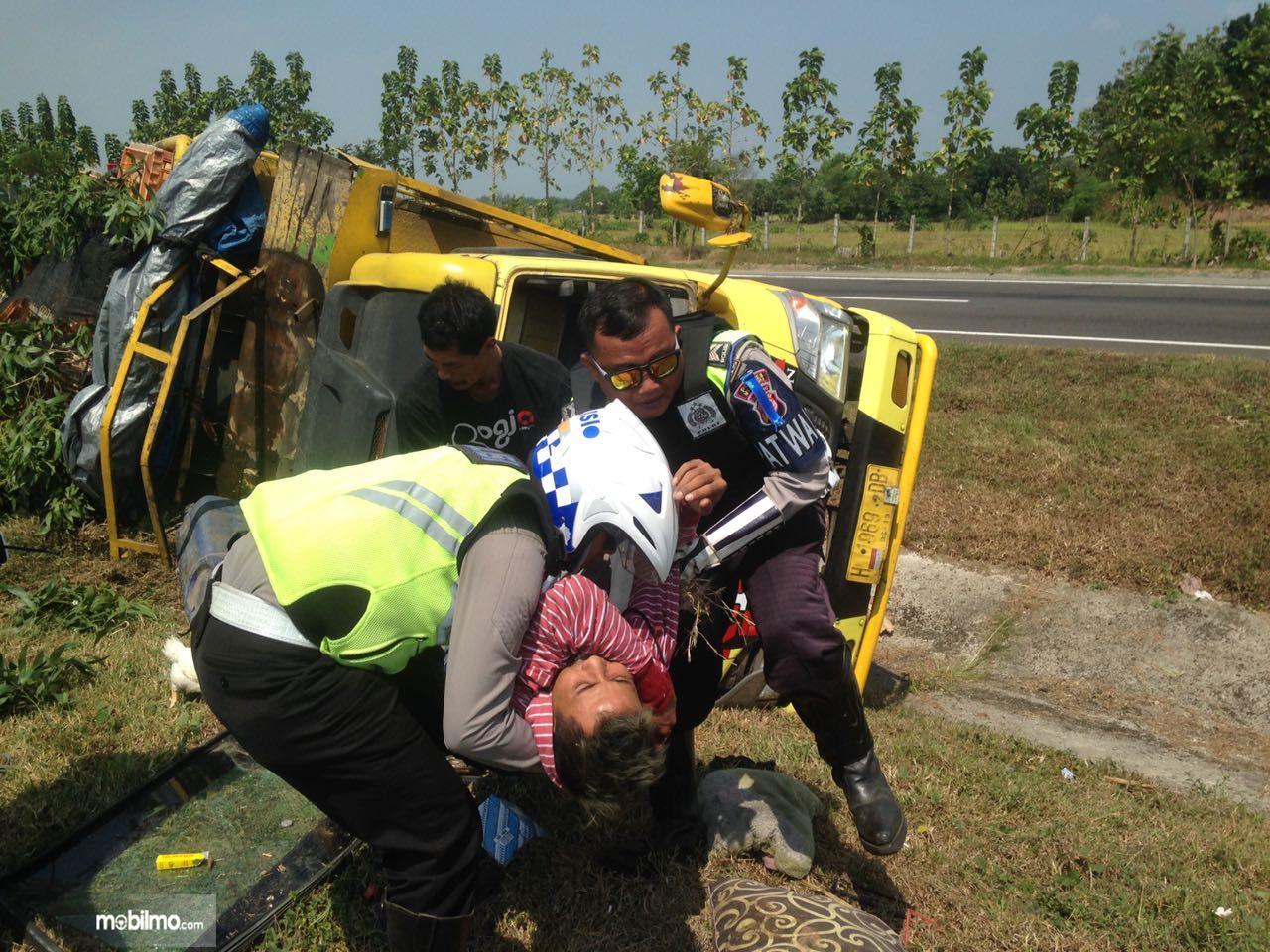 Foto polisi mengangkat korban truk terguling karena sopir mengantuk