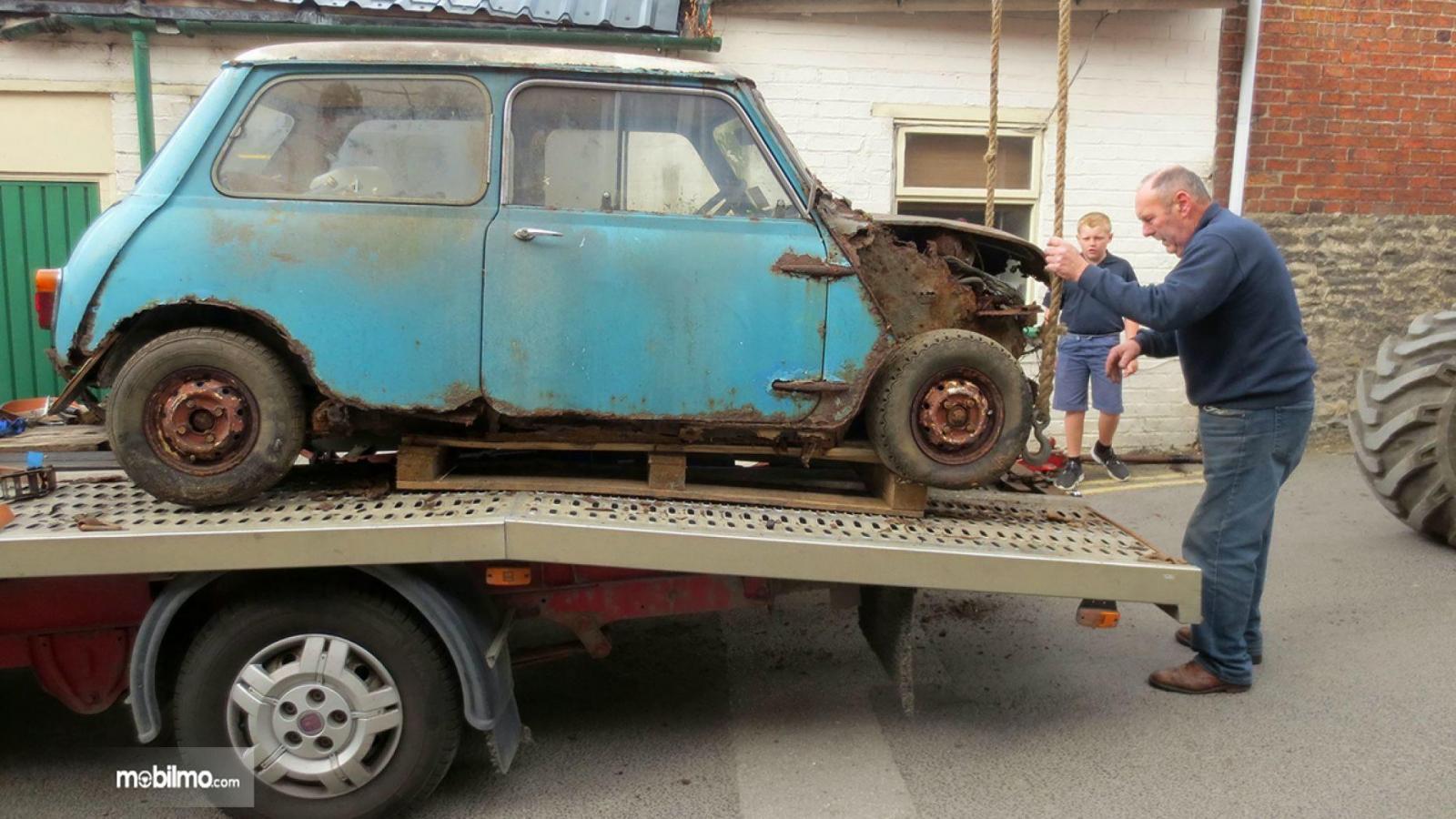 Gambar yang menunjukan melihat Mini Cooper yang rusak