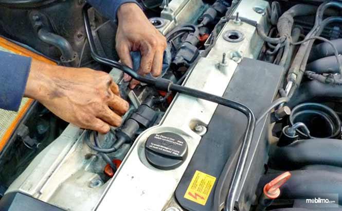 Tampak ilustrasi mekanik sedang mempersiapkan proses turun mesin pada mobil