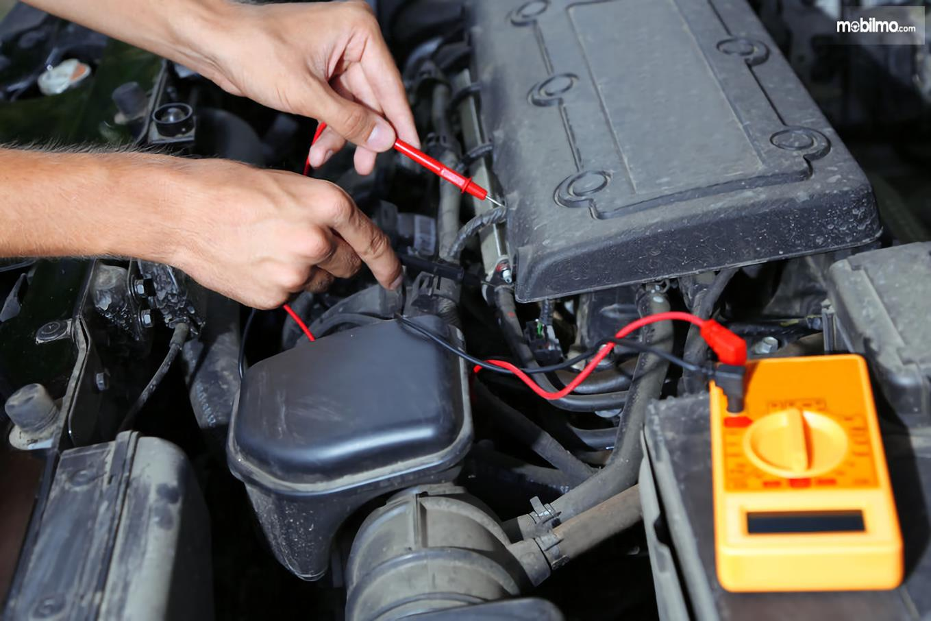 Tampak seorang mekanik sedang mengetes koil mati atau tidak dengan voltmeter