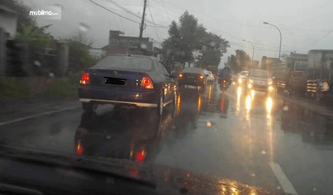 Gambar ini menunjukkan banyak mobil melaju di jalanan menjelang malam dalam kondisi jalanan yang basah