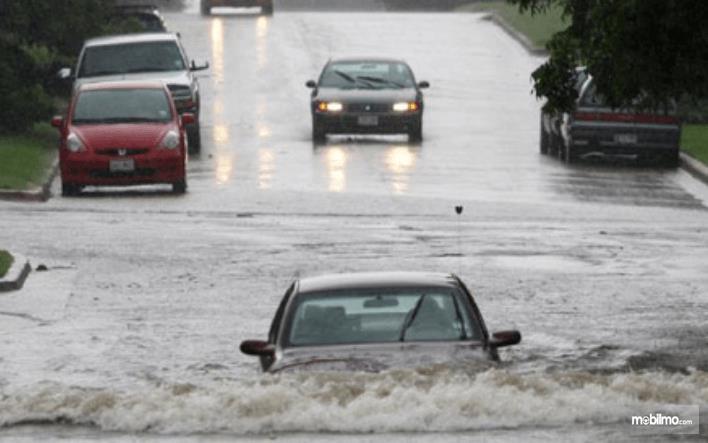 Gambar ini menunjukkan 1 mobil menerjang banjir dan beberapa mobil di jalanan yang tidak ada airnya