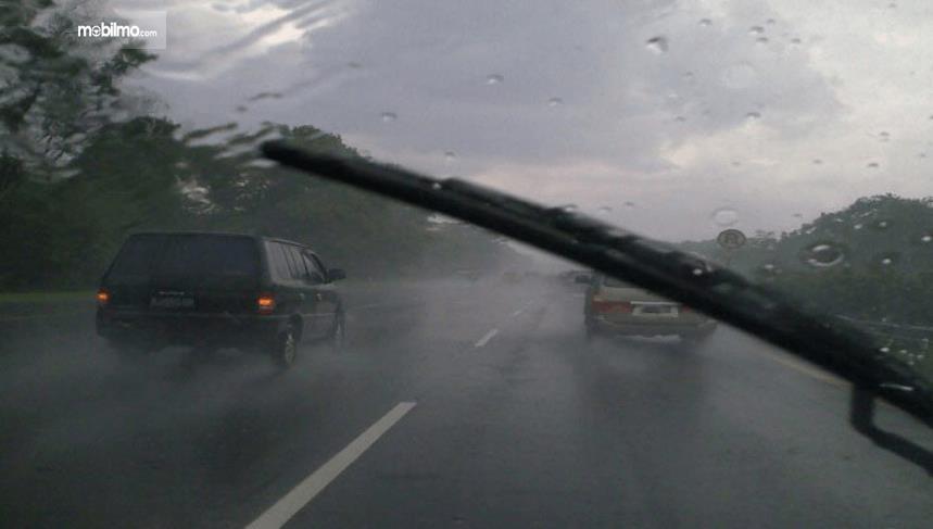 Gambar ini menunjukkan kaca mobil sedang diseka oleh wiper dan terdapat mobil lain di depannya