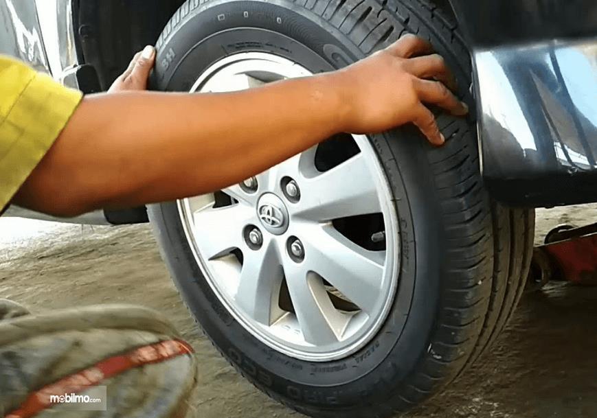 Gambar ini menunjukkan 2 buah tangan memegang ban mobil dan terlihat juga velg dengan warna silver