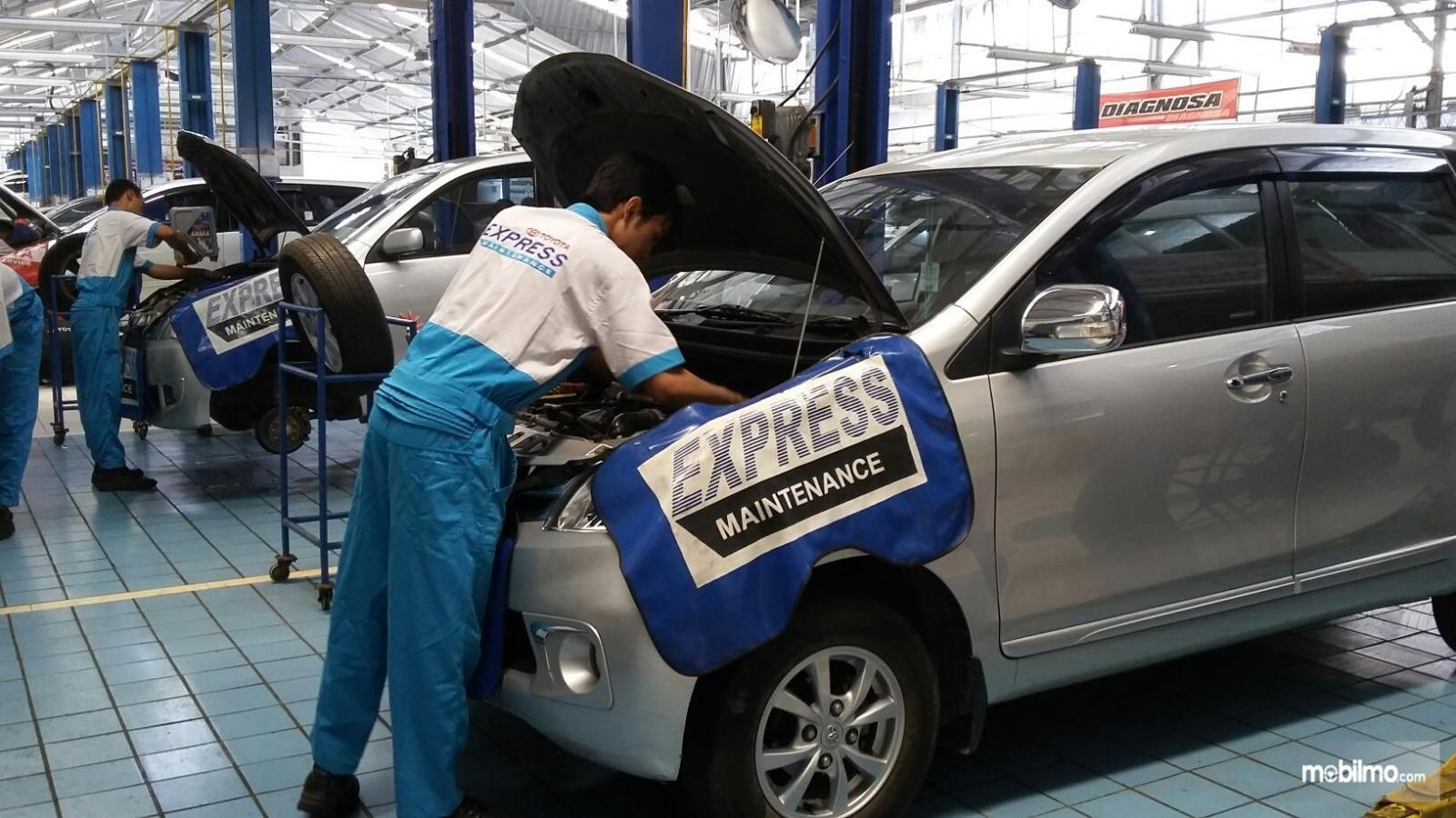 Foto mekanik Toyota sedang melakukan tugasnya