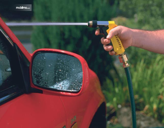 Gambar ini menunjukkan sebuah mobil yang disemprot menggunakan air bertekanan dengan alat khusus yang dipegang satu tangan