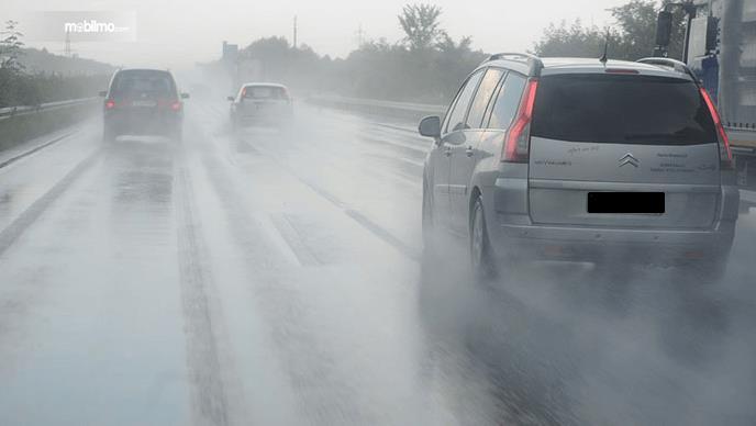 Gambar ini menunjukkan beberapa mobil sedang melewati jalanan dalam kondisi basah kuyup habis turun hujan