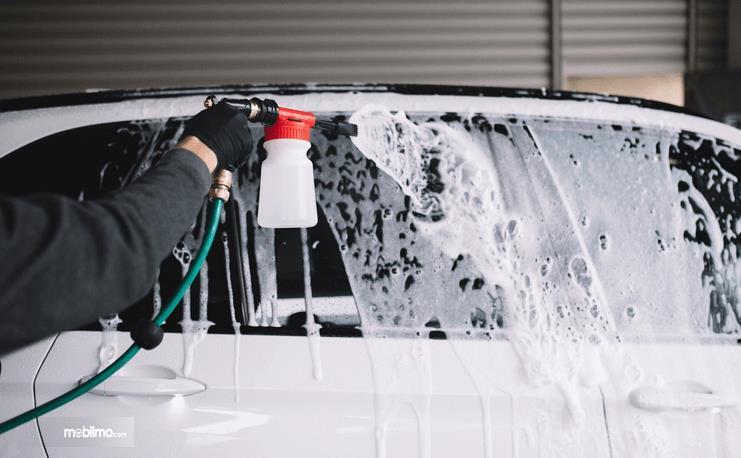 Gambar ini menunjukkan sebuah tangan memegang alat penyemprot air pada bodi mobil yang berbusa