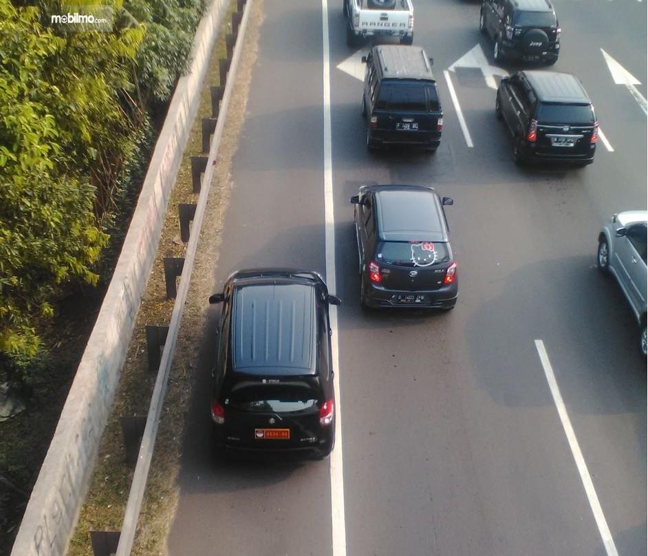 Foto mobil hitam menyalip menggunakan bahu jalan
