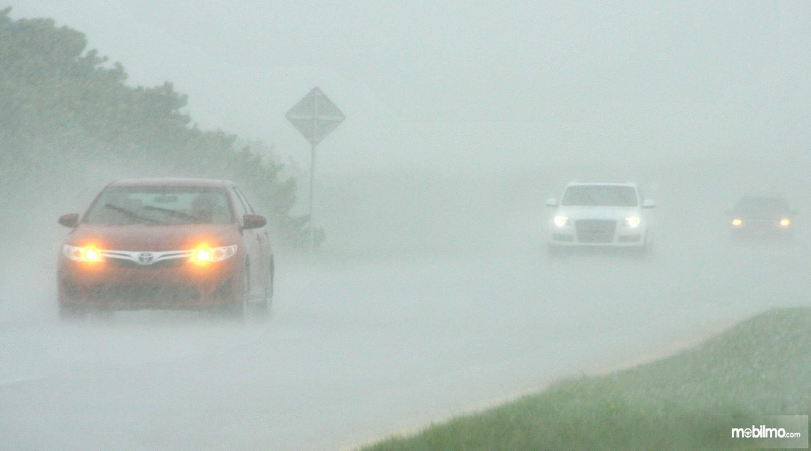 Foto mobil menyalakan lampu hazard di tengah hujan