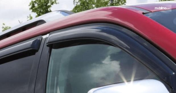 Gambar ini menunjukkan mobil warna merah dengan door visor warna hitam dan terlihat kaca mobil