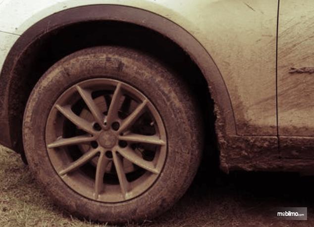 Gambar ini menunjukkan ban, velg dan bodi mobil dalam kondisi kotor