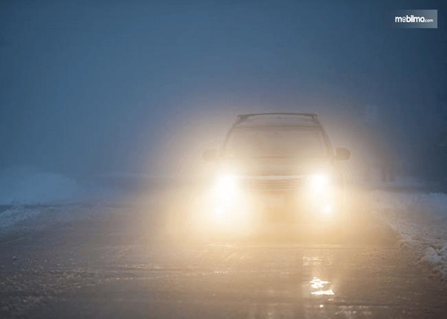 Gambar ini menunjukkan sebuah mobil yang sedang berjalan menembus kabut dengan lampu depan menyala