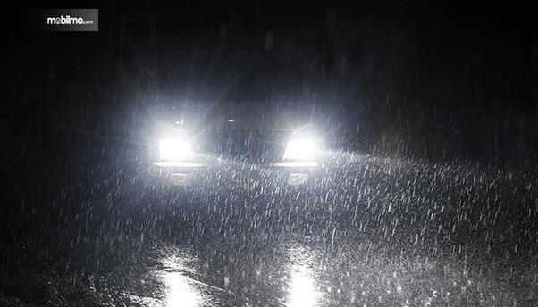 Gambar ini menunjukkan sebuah mobil dengan lampu menyala dengan keadaan hujan turun