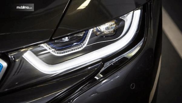 Gambar ini menunjukkan lampu utama pada mobil warna hitam