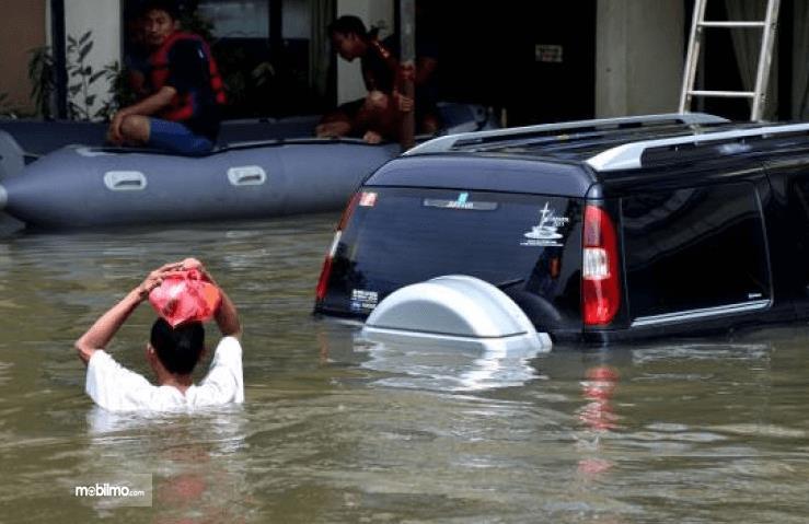 Gambar ini menunjukkan mobil terendam banjir dan terdapat seseorang yang juga di dalam banjir