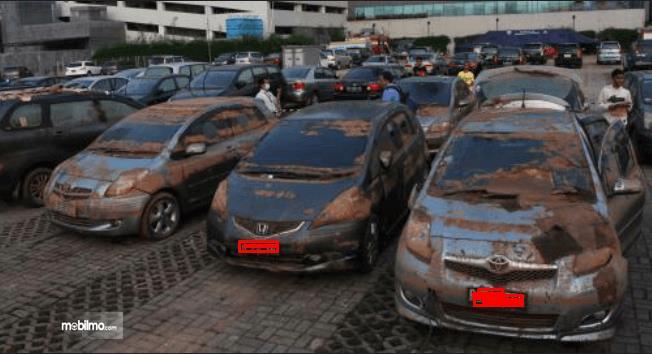 Gambar ini menunjukkan banyak mobil dalam keadaan kotor habis terkena banjir