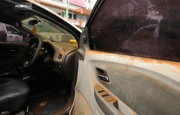 Gambar ini menunjukkan bagian kemudi dan pintu mobil yang kotor habis terkena banjir