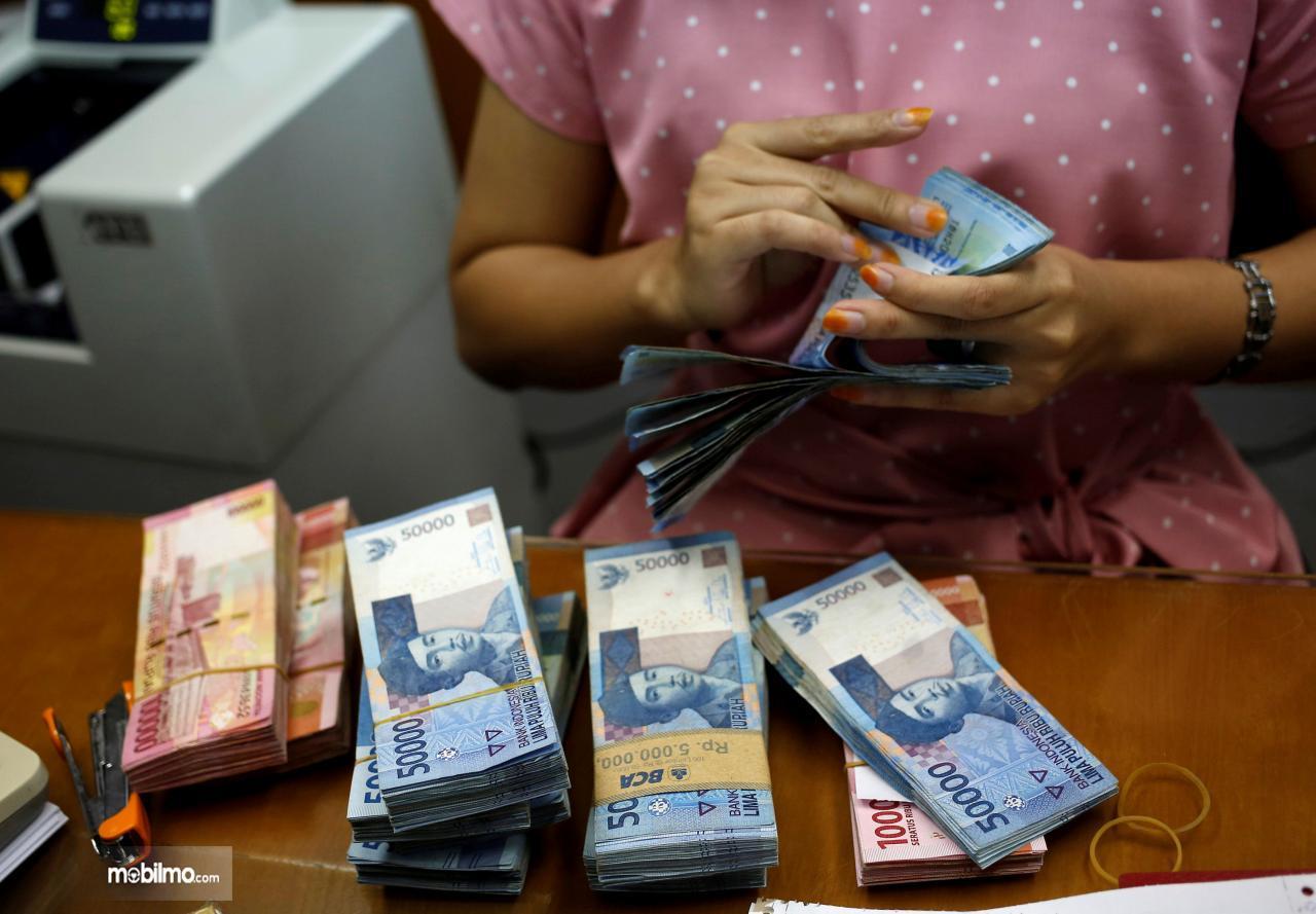 Foto petugas bank sedang menghitung uang