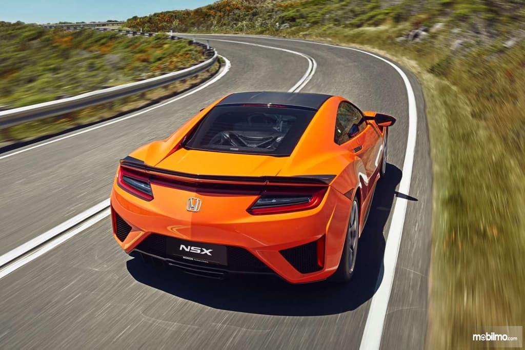 Gambar mobil Honda NSX 2019 berwarna orange dilihat dari sisi depan yang sedang berjalan di jalan Indonesia
