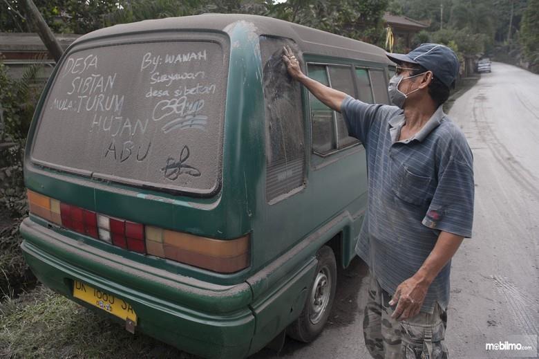 Foto seorang bapak sedang mengelap mobil yang kotor