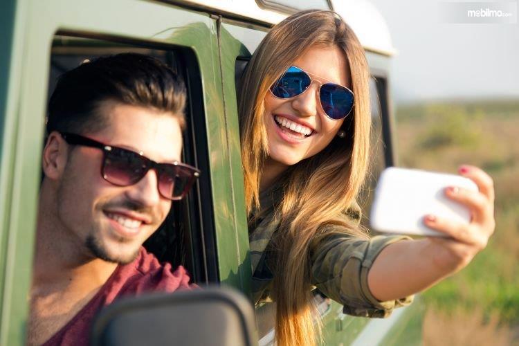Foto sepasang pria wanita selfie di mobil