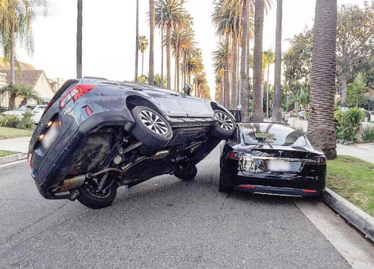 Foto Subaru parkir di atas Tesla Model S