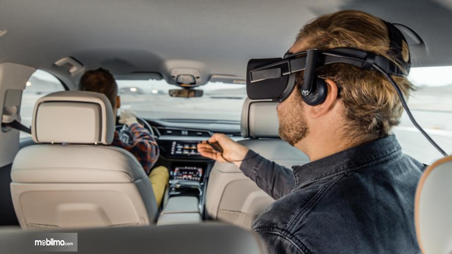 penumpang belakang yang sedang memainkan teknologi VR Audi