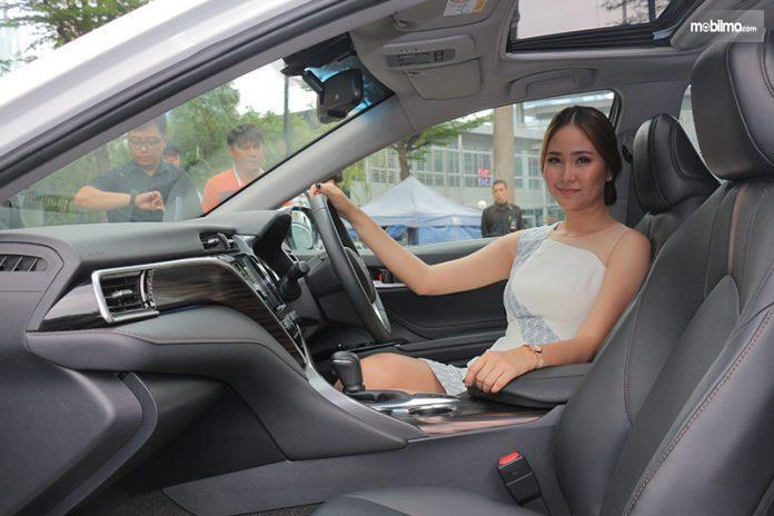 Seorang model berpose di dalam All New Toyota Camry 2019