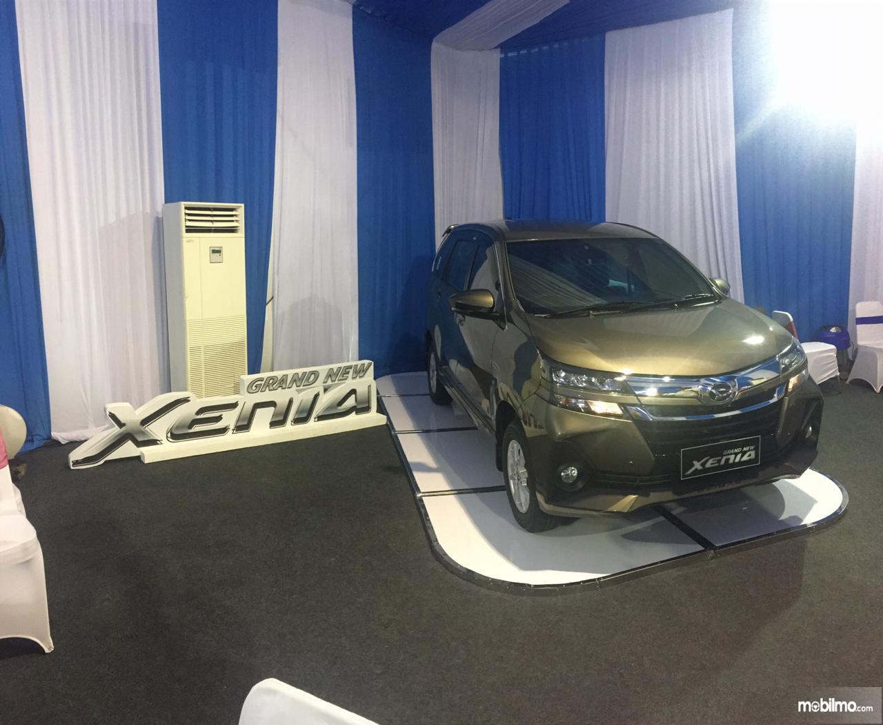 Gambar mobil Daihatsu Grand New Xenia R A/T 1.3 2019 berwarna kuning dilihat dari sisi depan
