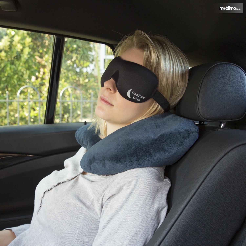 Foto seorang wanita tidur di mobil