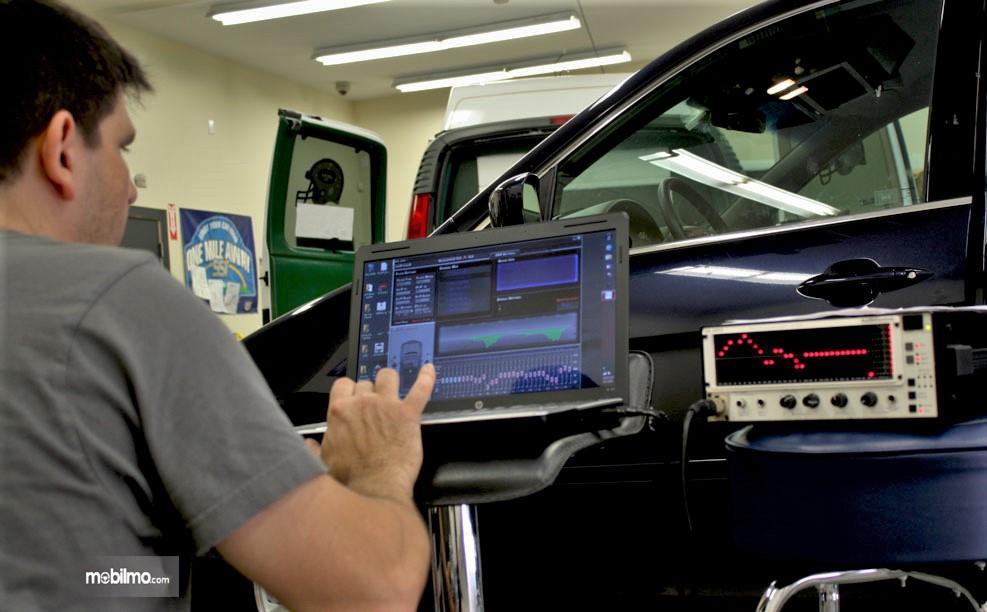 Foto seseorang melakukan setting sistem audio mobil