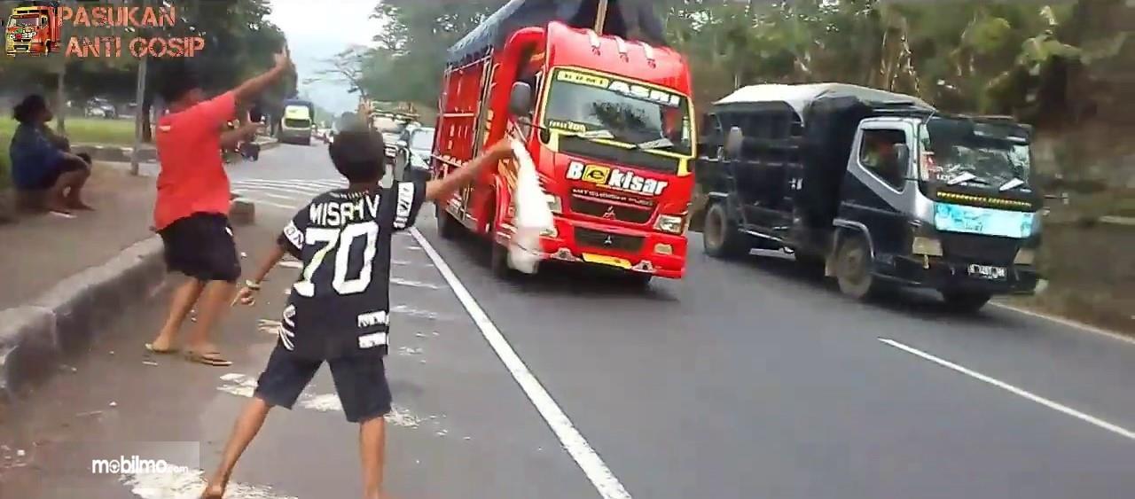 Foto anak-anak meminta sopir truk lakukan goyang kapten oleng