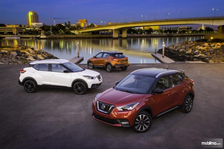 Gambar tiga mobil Nissan Kicks 2019 berwarna merah, putih dan orange sedang parkir di depan sungai yang indah