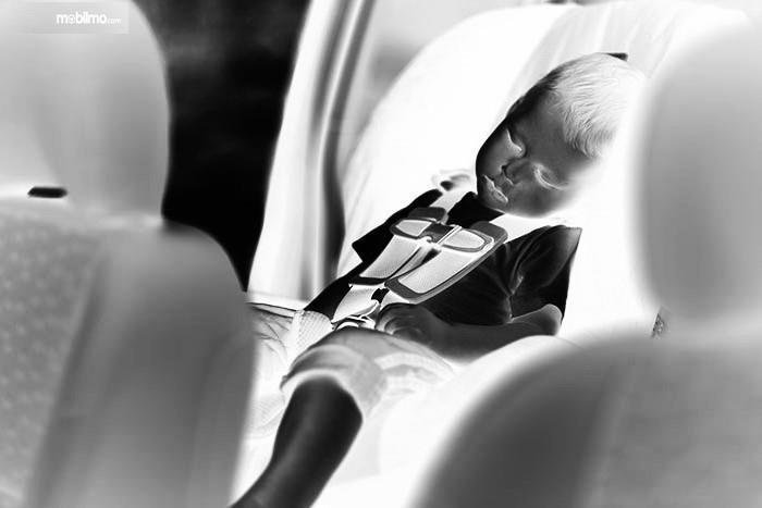 Gambar ilustrasi seorang anak tertidur di dalam mobil