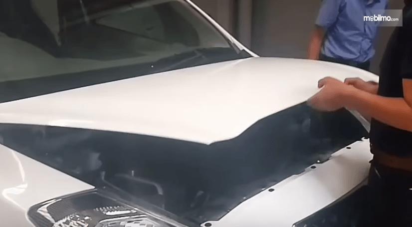 Gambar ini menunjukkan 2 buah tangan memegang kap mesin mobil warna putih