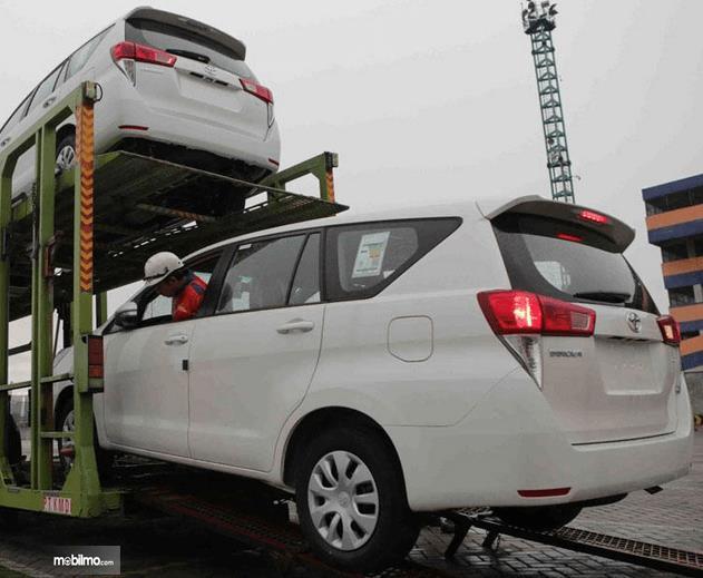 Gambar ini menunjukkan mobil Toyota warna putih sedang dinakkan ke kendaraan pengangkut