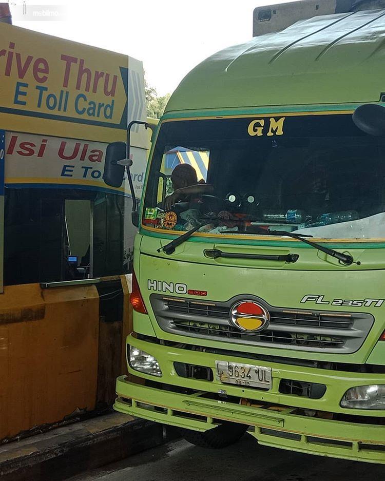 Foto pengemudi truk sedang isi ulang kartu tol
