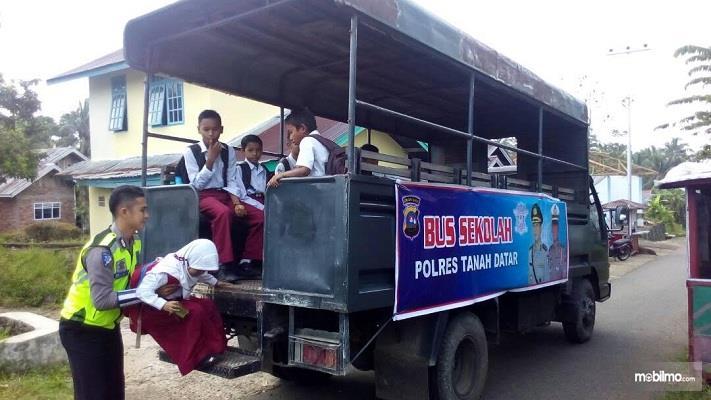 Foto pak Polisi membantu anak naik ke truk bus sekolah